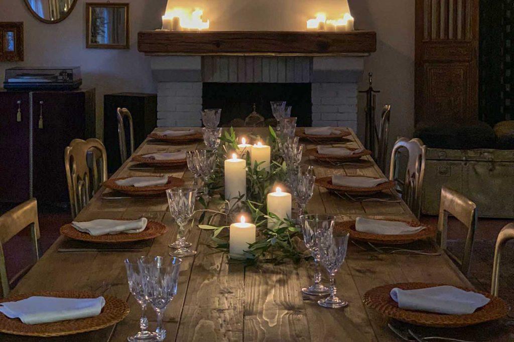 Una tavola semplice ma di grande stile con candele accese per una mise en place d'effetto
