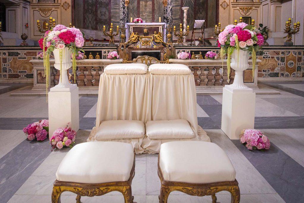 Tessuti eleganti e fiori con colori tenui per i posti riservati agli sposi in chiesa
