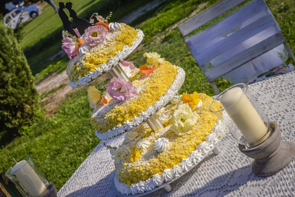 La torta mimosa con il caratteristico giallo adornato di crema bianca finemente lavorata