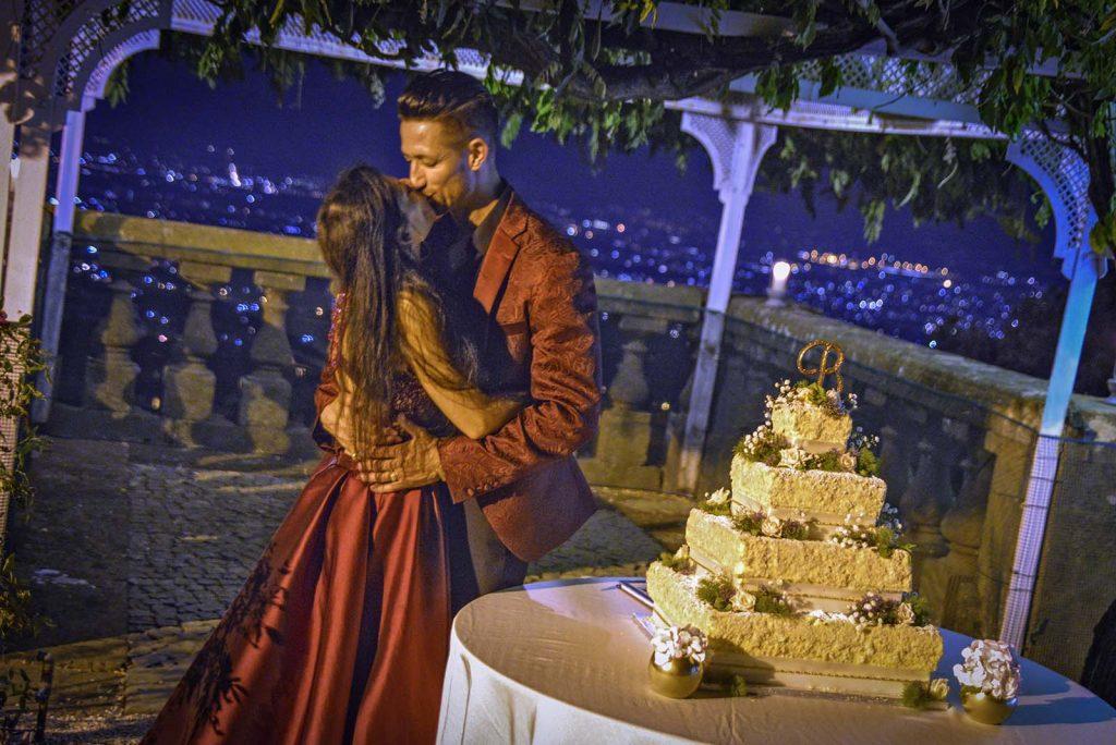 Gli sposi si abbracciano felici su uno splendido panorama nel quale troneggia un'imponente torta di nozze