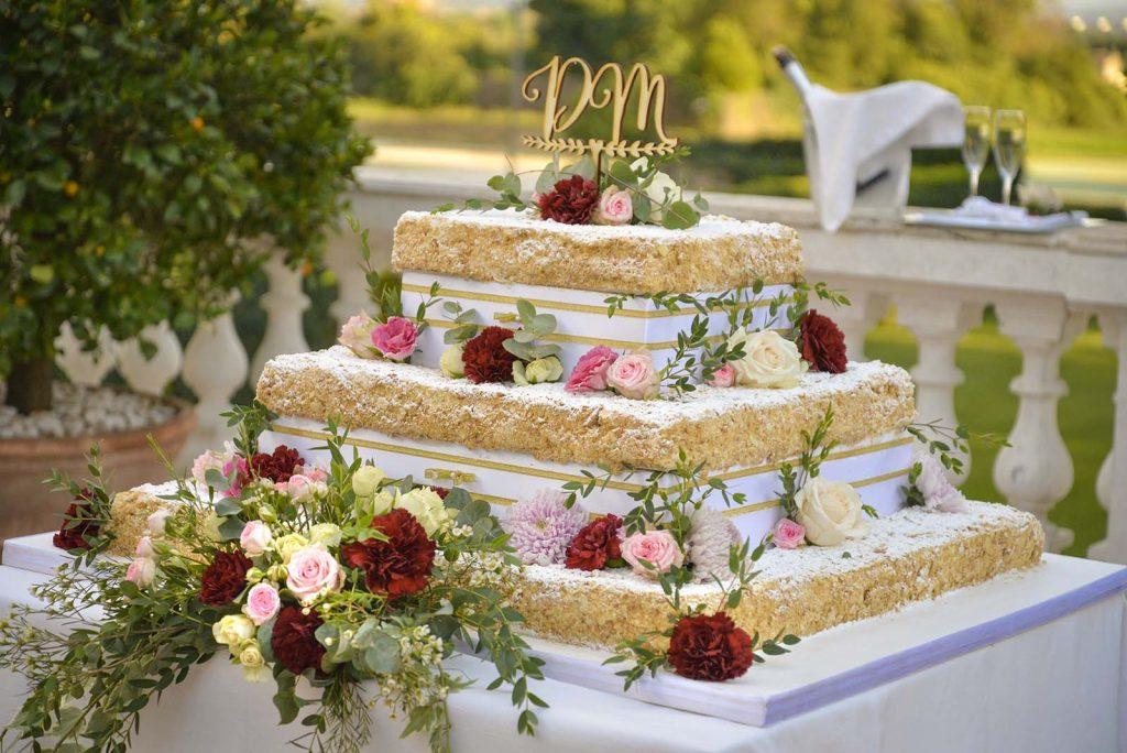 Un'originale torta quadrata di nozze, finemente impreziosita con fiori colorati