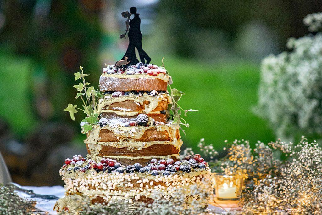 Torta nuziale con la miniatura degli sposi in cima, sopra tanta arte pasticcera